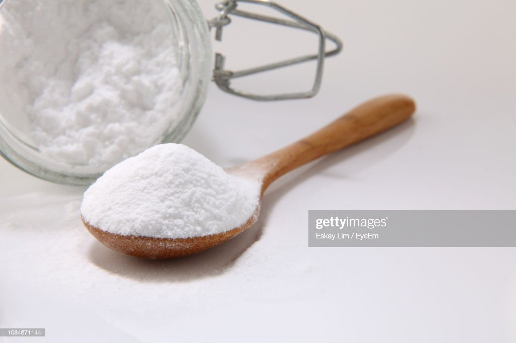 Close-Up Of Baking Soda In Wooden Spoon And Jar On White Background : Stock Photo