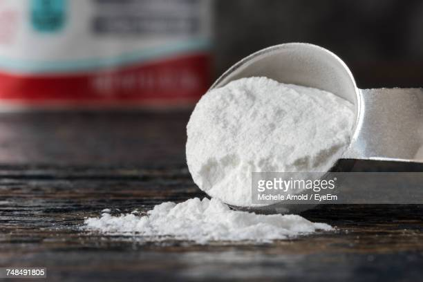 Close-Up Of Baking Soda Spilled From Measuring Spoon On Table