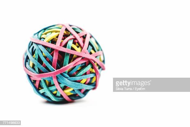 Close-Up Of Ball Made With Colorful Rubber Bands Against White Background
