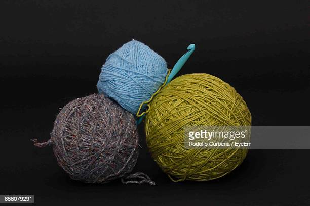 Close-Up Of Ball Of Wools Against Black Background