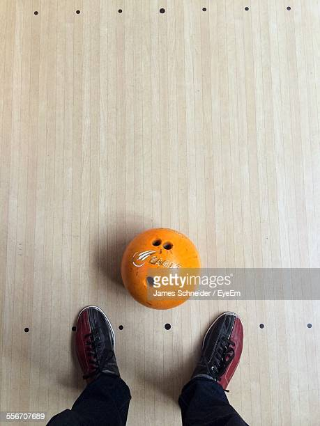 close-up of ball with human legs in bowling alley - bowling alley stock pictures, royalty-free photos & images