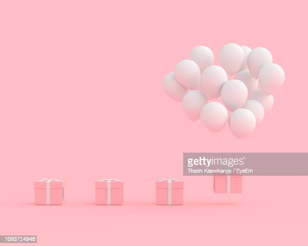 close-up of balloons and gift box against pink background - still life not people stock photos and pictures