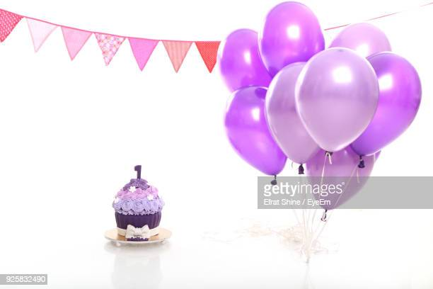 Close-Up Of Balloons By Birthday Cake With Bunting Against White Background