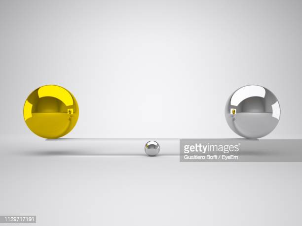 close-up of balls balancing against white background - gleichheit stock-fotos und bilder