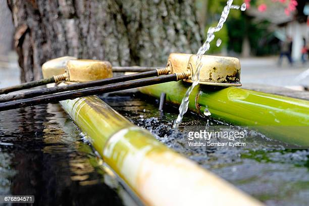 close-up of bamboo dipper water fountain with ladles - bamboo dipper stock photos and pictures
