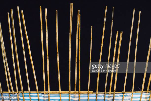 close-up of bamboo sticks against black background - black bamboo stock pictures, royalty-free photos & images