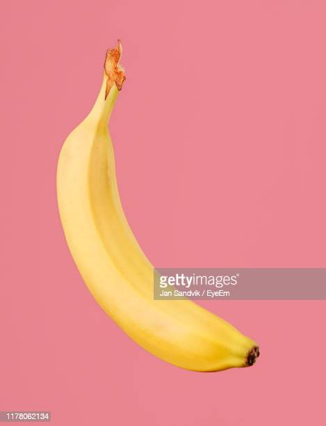 close-up of banana against pink background - banana stock pictures, royalty-free photos & images