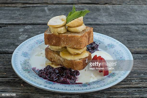 Close-Up Of Banana Sandwich Served In Plate On Wooden Table