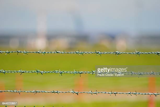 Close-Up Of Barbed Wire Against Blurred Background