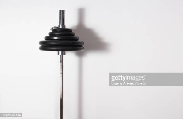 close-up of barbell against white wall - barbell stock pictures, royalty-free photos & images