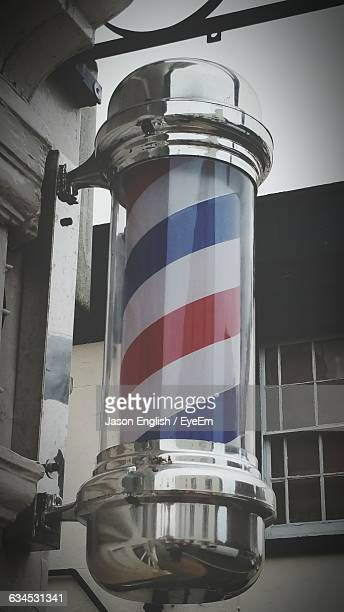 close-up of barber shop pole on wall - barber pole stock photos and pictures