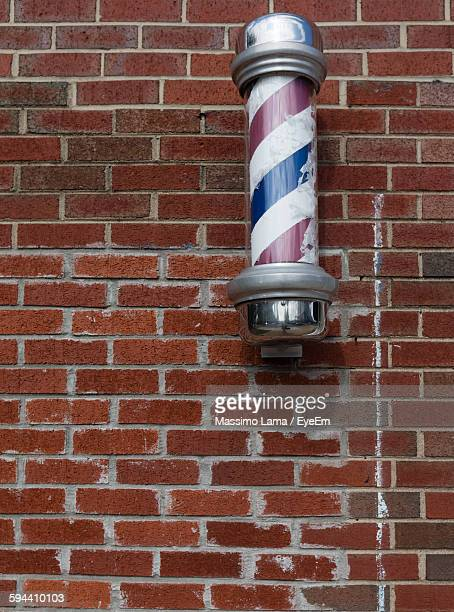 close-up of barbers pole on brick wall - barber pole stock photos and pictures