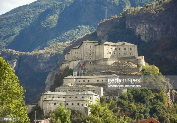 Close-up of Bard Fortress on top of a high hill surrounded by Alpine landscape in Bard, Valle d'Aosta, Italy