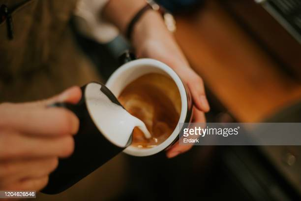 close-up da mão barista enquanto faz menu de bebida espumosa - café casa de comes e bebes - fotografias e filmes do acervo