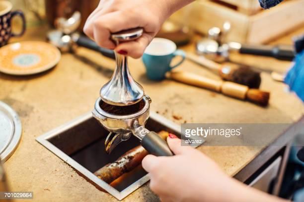 Portafilter でコーヒーを押すとバリスタのクローズ アップ