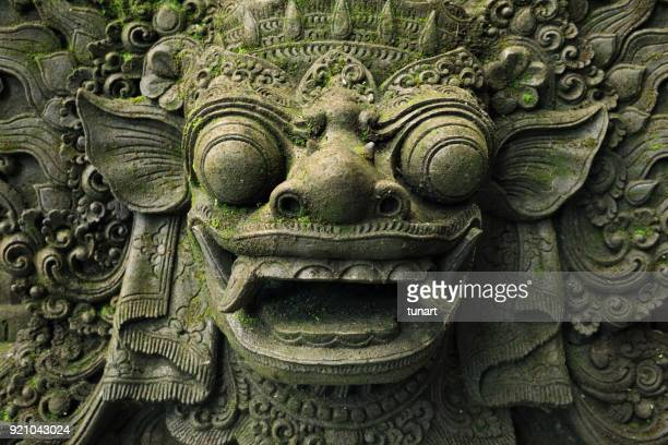 Close-up of Barong Lion Guard's Face, Mossy Statue of Balinese Mythological Hero Carved From Stone