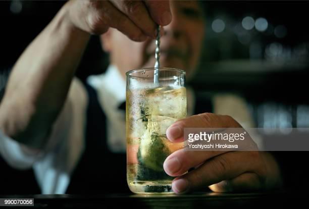 close-up of bartender hand pouring cocktail - kombination stock-fotos und bilder