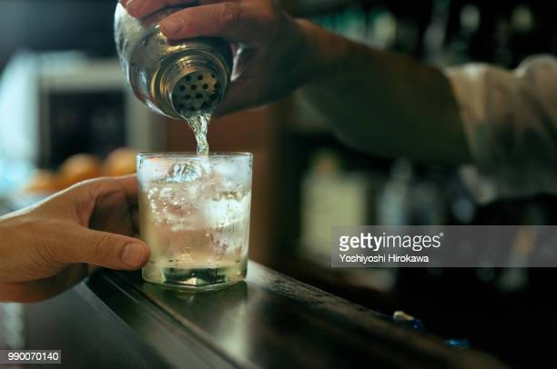 close-up of bartender hand pouring cocktail - cocktail stock pictures, royalty-free photos & images