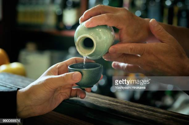 close-up of bartender hand pouring sake to glass which hands of adult man. - saki stock photos and pictures