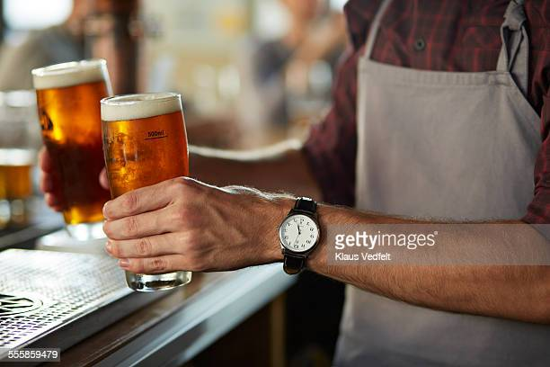 close-up of bartender serving beers at bar - beer glass stock pictures, royalty-free photos & images