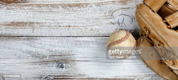 close-up of baseball ball and glove on wooden table - baseball glove stock pictures, royalty-free photos & images