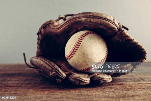 close-up of baseball ball in glove on table - baseball glove stock pictures, royalty-free photos & images
