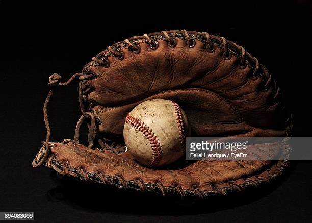 Close-Up Of Baseball Glove And Ball On Black Background