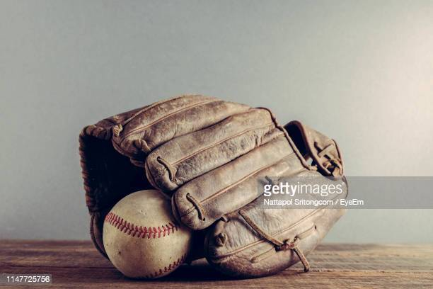 close-up of baseball glove and ball on table - baseball glove stock pictures, royalty-free photos & images