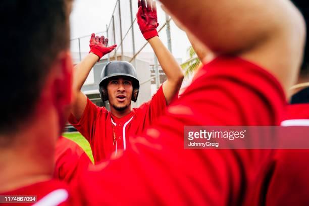 close-up of baseball teammates congratulating scoring player - baseball team stock pictures, royalty-free photos & images