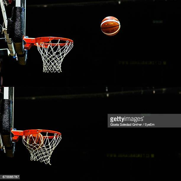 close-up of basket ball reaching basket - basketball hoop stock pictures, royalty-free photos & images