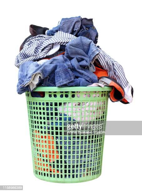 close-up of basket full of laundry against white background - hamper stock pictures, royalty-free photos & images