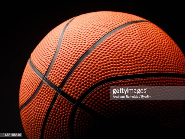 close-up of basketball against black background - basketball ball stock pictures, royalty-free photos & images
