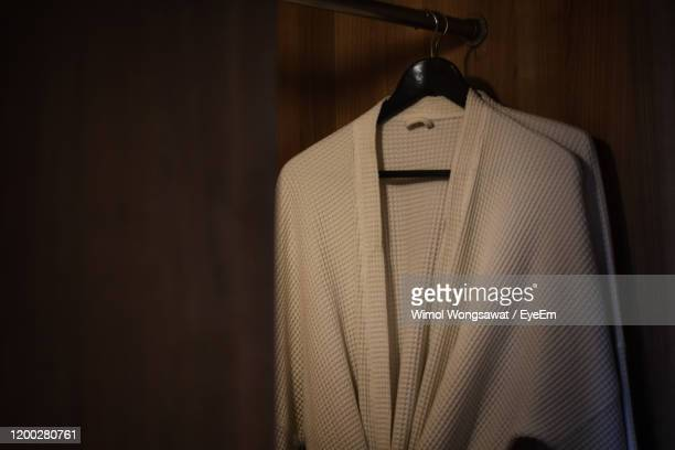 close-up of bathrobe hanging on clothes rack - bathrobe stock pictures, royalty-free photos & images