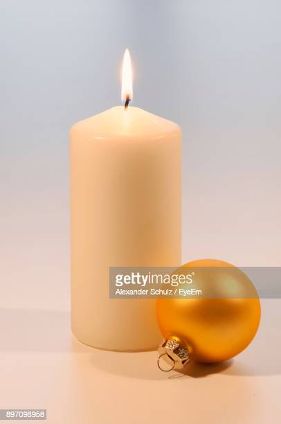 Close-Up Of Baubles With Burning Candle On White Background