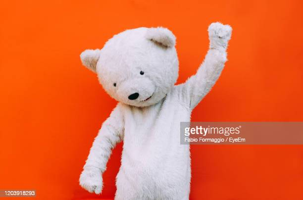 close-up of bear gesturing against orange background - bear suit stock pictures, royalty-free photos & images