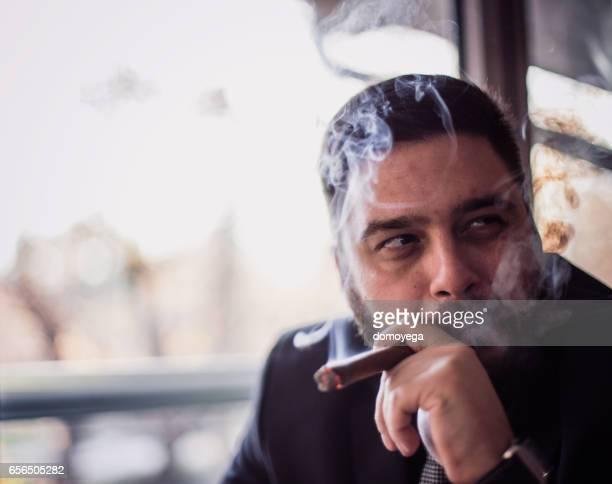 Close-up of bearded caucasian man smoking a cigar