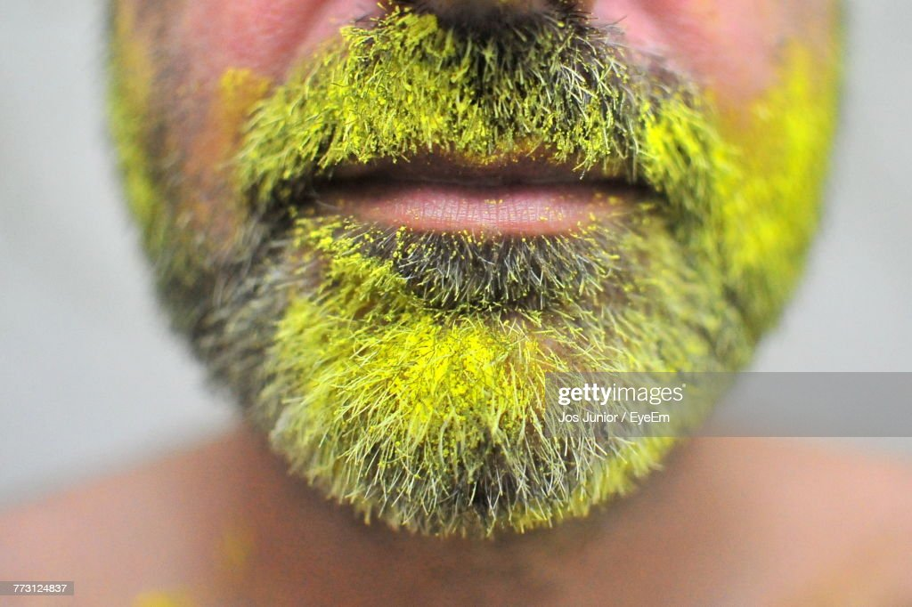 Close-Up Of Bearded Man With Yellow Paint : Stock Photo