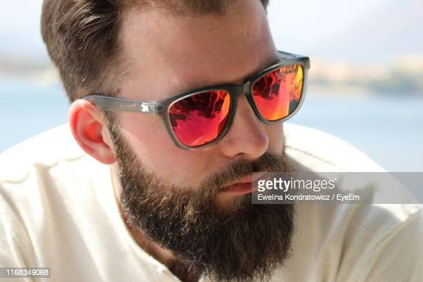 close-up of bearded young man wearing sunglasses while looking away outdoors - サングラス 男性 ストックフォトと画像