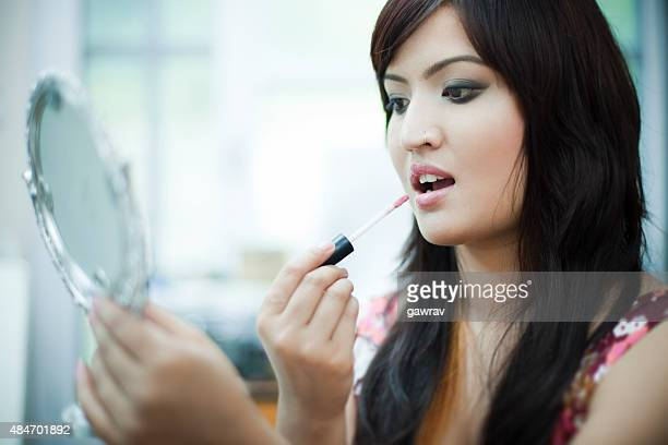 Close-up of beautiful Asian woman doing makeup with lip gloss.
