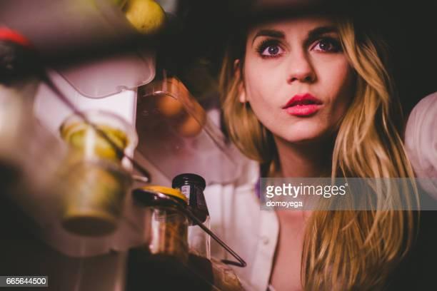 Närbild av vacker blond kvinna som tittar i kylskåp