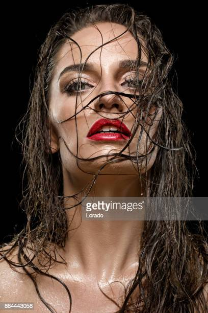 Close-Up of beautiful female face covered in wet hair