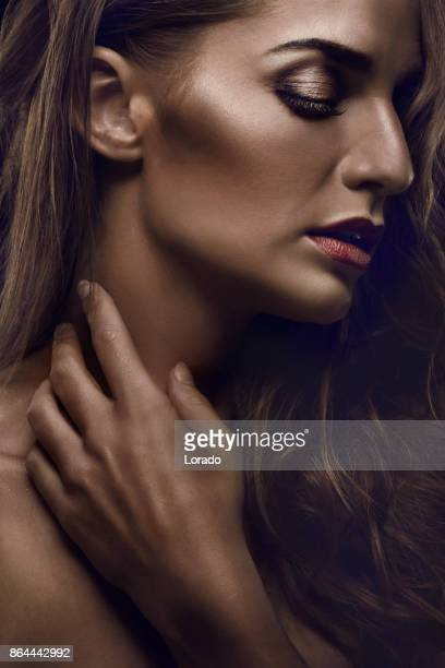 close-up of beautiful glossy female face against dark background - clavicle stock photos and pictures