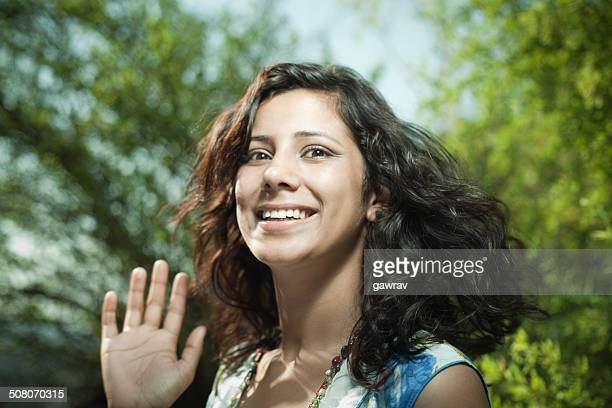 Close-up of beautiful, happy young woman waving hand in nature.