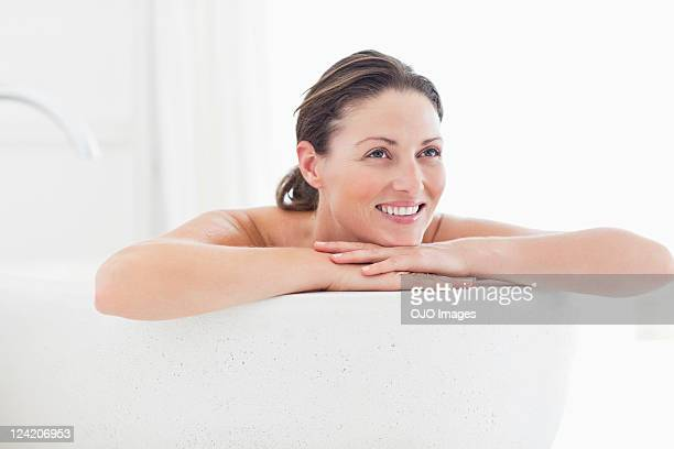 Close-up of beautiful mid adult woman smiling in bathtub
