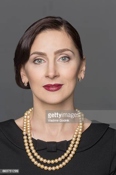 Close-up of beautiful woman against gray background