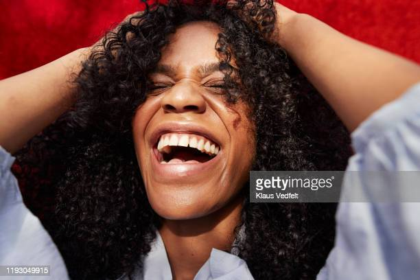 close-up of beautiful woman against red wall - lachen stockfoto's en -beelden