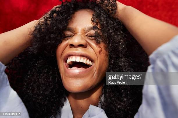 close-up of beautiful woman against red wall - reírse fotografías e imágenes de stock