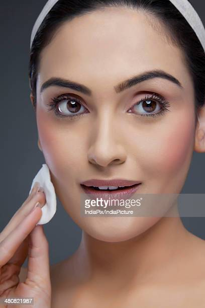 Close-up of beautiful woman applying compact powder over blue background