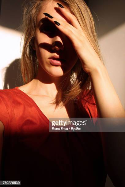 Close-Up Of Beautiful Woman Covering Face With Hand