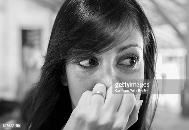 Close-Up Of Beautiful Woman Covering Her Mouth